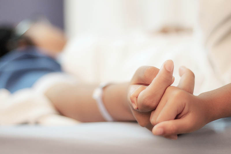 holding hands on a bed