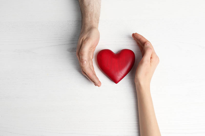 Couple holding decorative heart on white wooden background