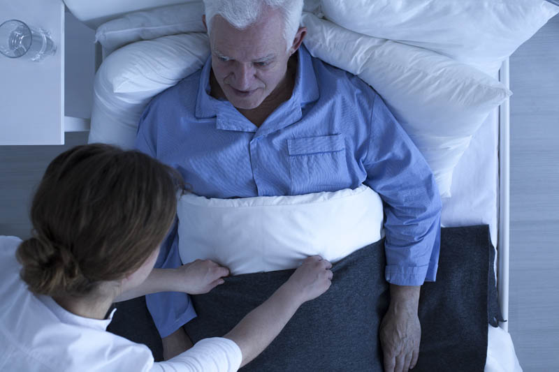 man laying on bed with nurse