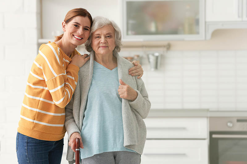 Elderly woman with female caregiver in kitchen